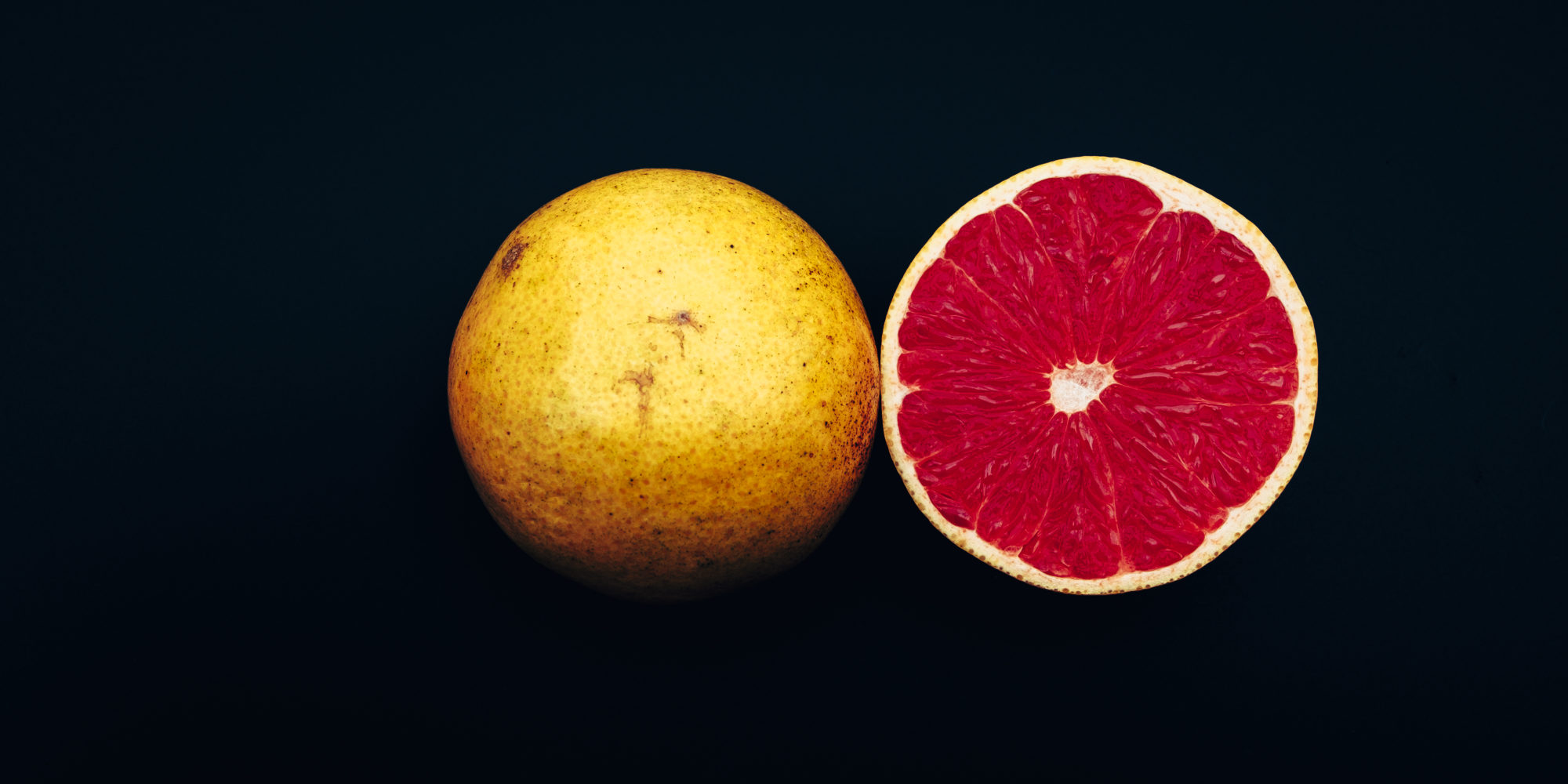 Fresh Grapefruit cut in half on a black background, Dinner in the Dark Motive