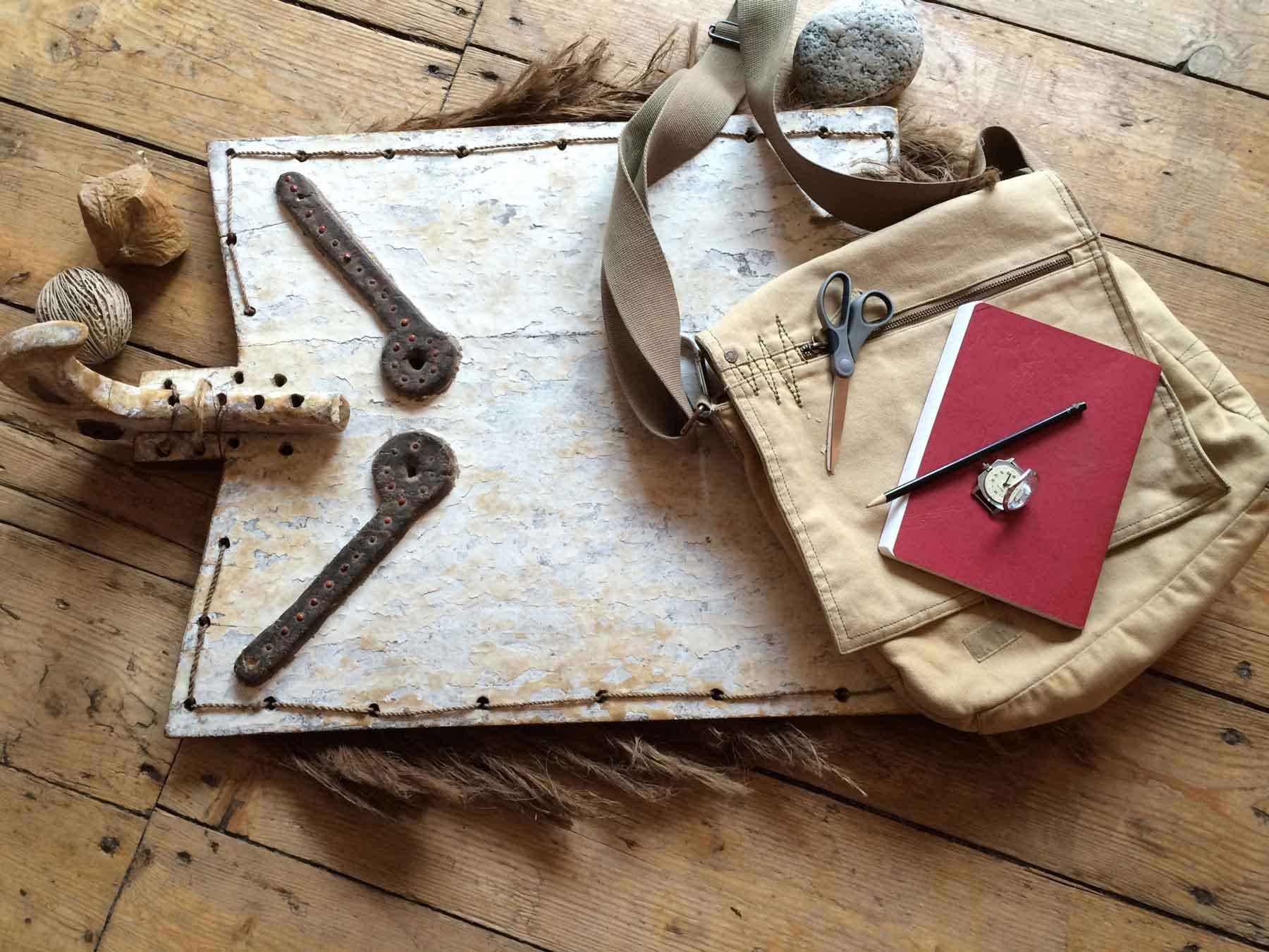Rucksack Stift, Notizbuch in Roter Farbe, Kompass und mythisches Motiv von oben gesehen auf erdigem, holzigem Untergrund