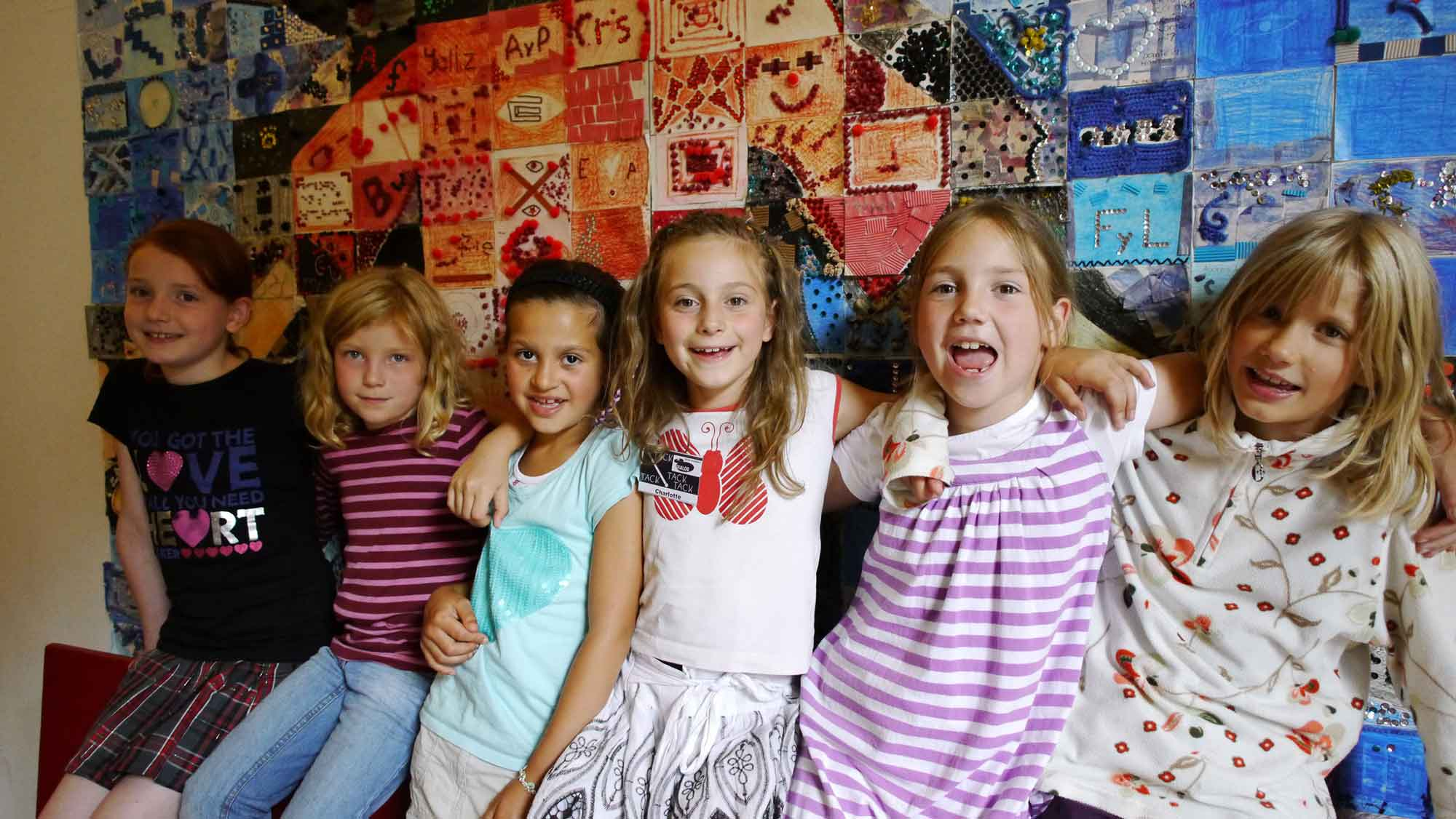 Eine Gruppe von Geburtstags Kindern vor einem bunten großen Bild im Dialoghaus