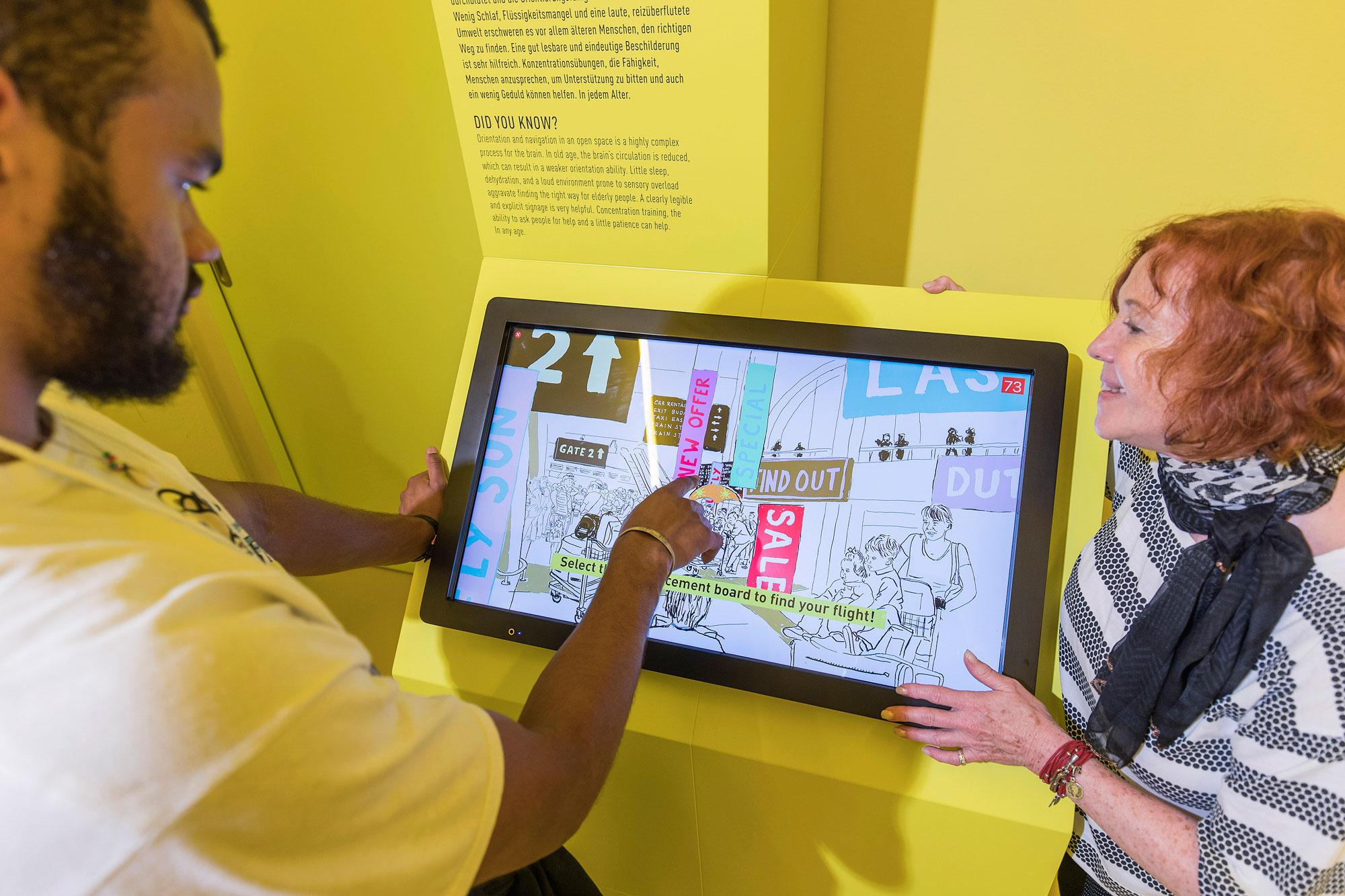 Junger Besucher im gelben Raum an der Station FlughafenTerminal. Ein Monitor zeigt schnell wechselnde Wege und viele Anzeigen im Flughafenterminal. Man muss auswählen welches der richtige für den eigenen Flug ist. neben dem Monitor steht eine Senior Guide.