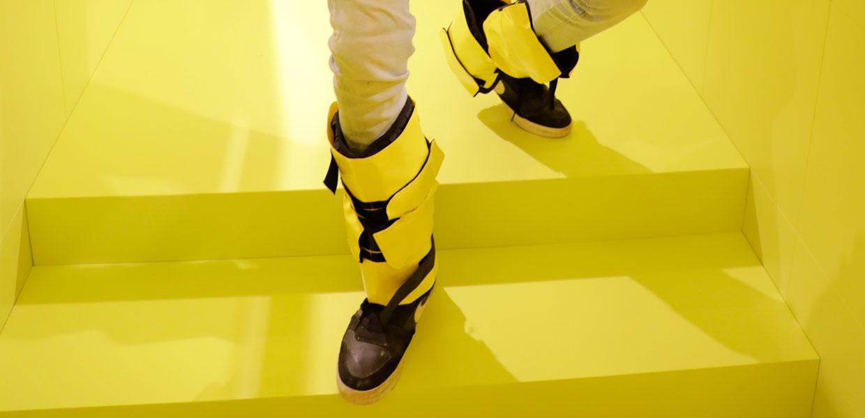 Besucher mit Gewichten an den Beinen geht eine gelbe Treppe herunter. Ein Motiv aus der Ausstellung Dialog mit der Zeit. copyright Andreas Lindlahr