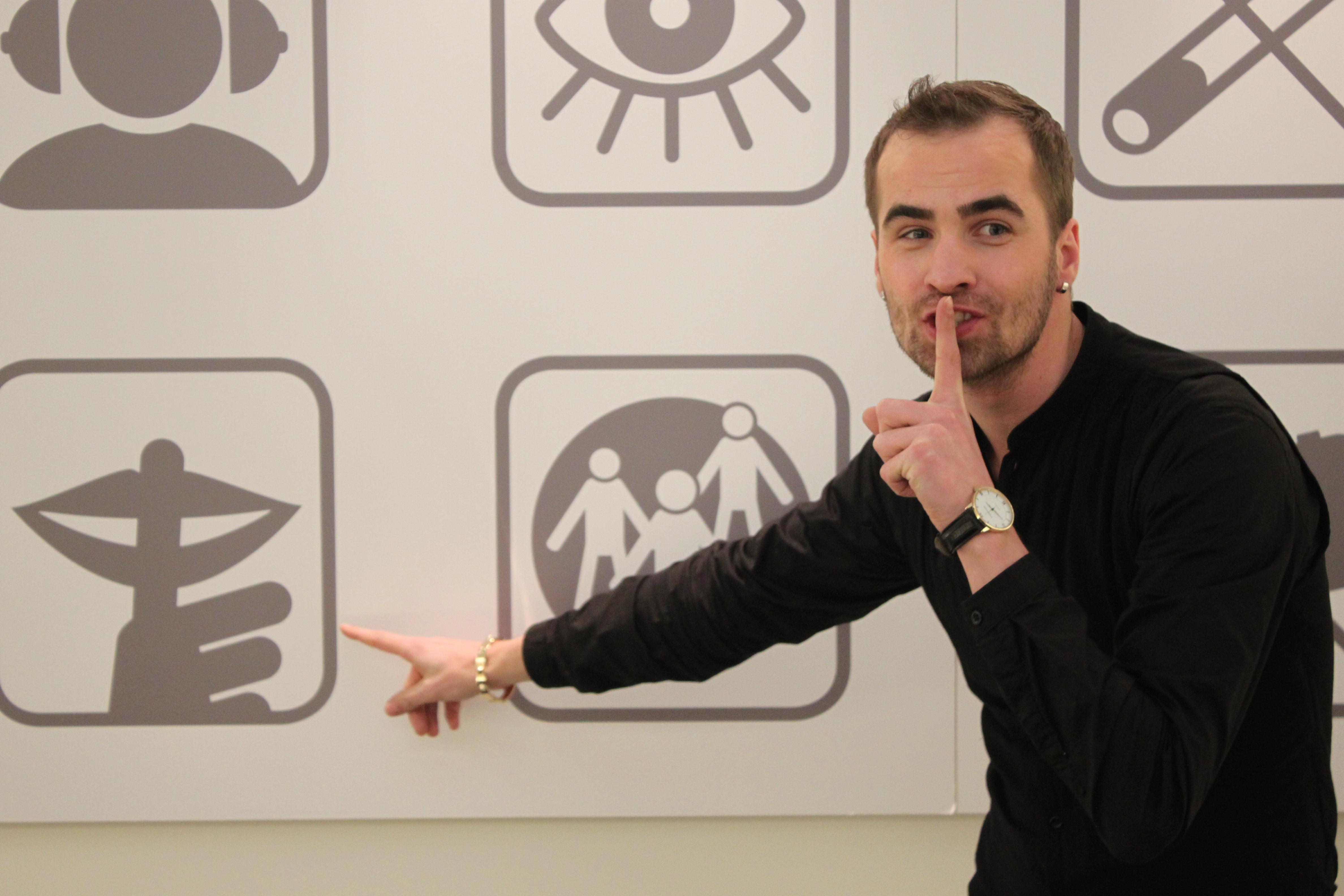 Guide Andres aus der Ausstellung Dialog im Stillen vor der Piktogramm Tafel