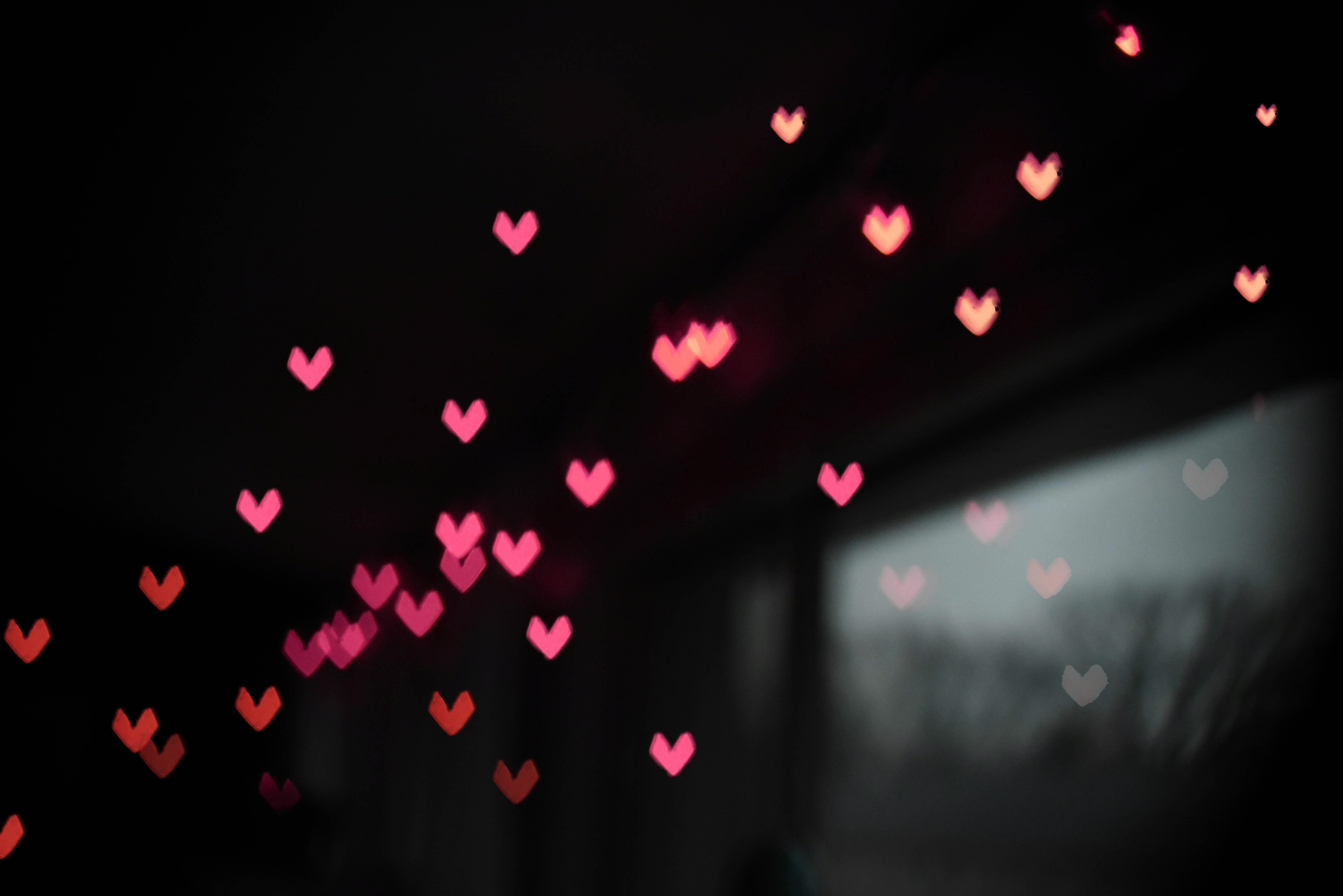 Pinke Herzen vor dunklem Hintergrund
