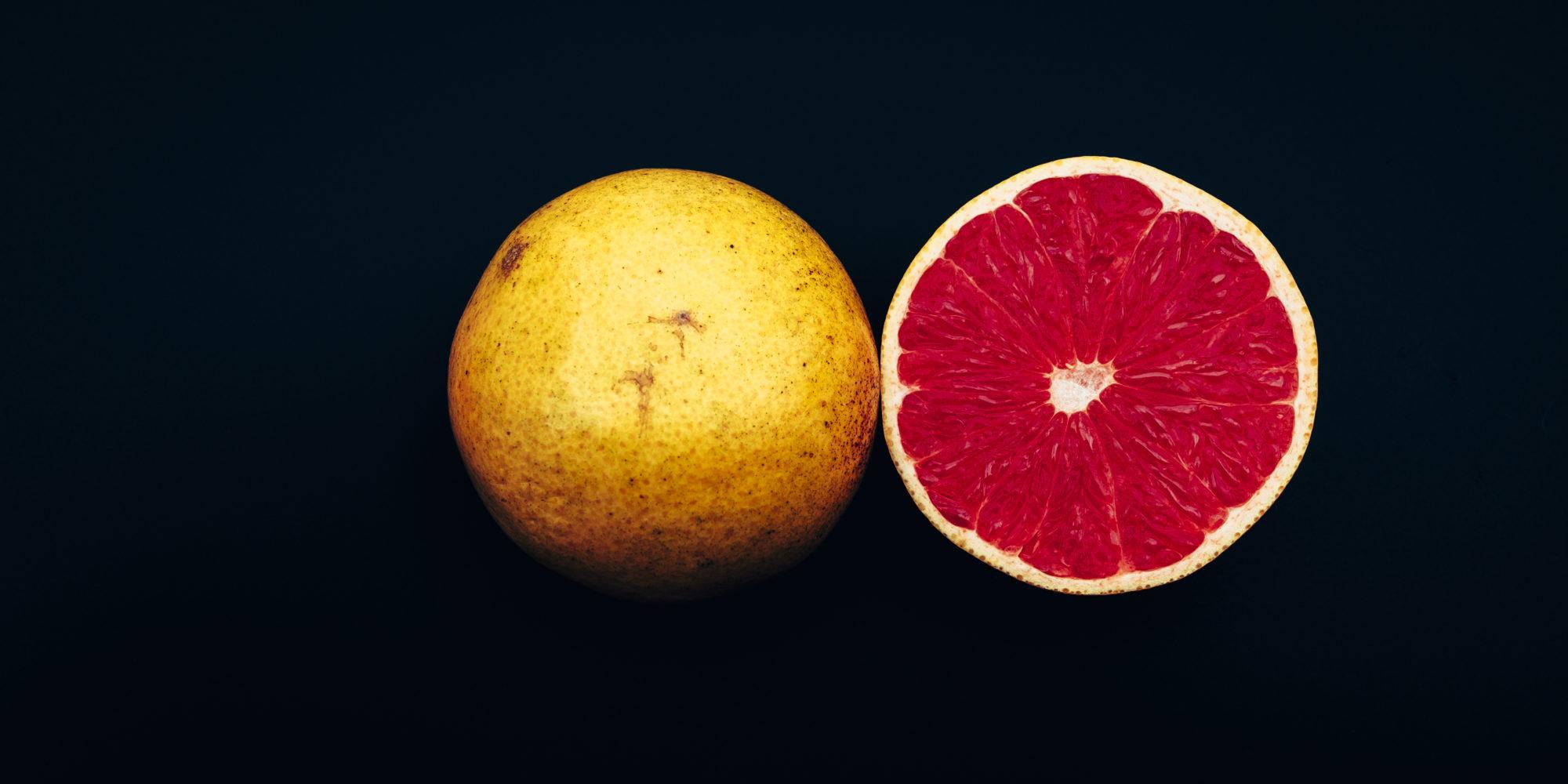 Frische Grapefruit halbiert vor schwarzem Hintergrund, Dinner in the Dark Motiv