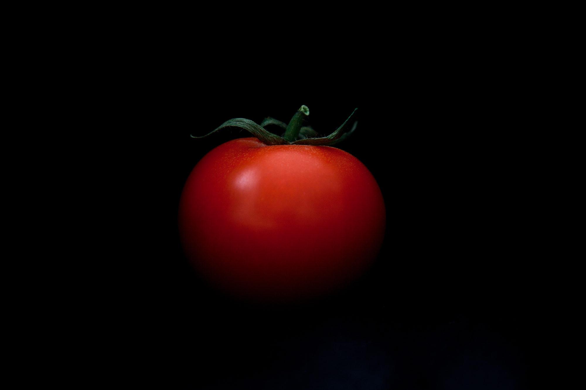 Tomate mit Strunck vor schwarzem Hintergrund, Dinner in the Dark Motiv
