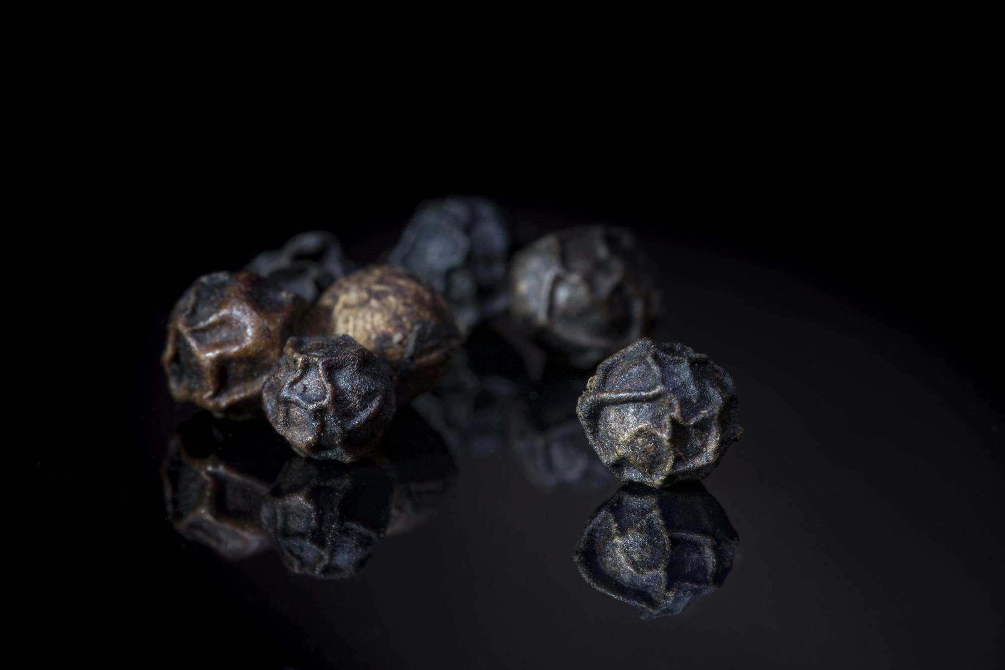 Schwarze Pfefferkörner auf schwarzem Hintergrund, Dinner in tthe Dark Motiv