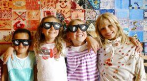 Kindergeburtstag 4 Mädchen mit Dunkelbrillen vor einem bunten Hintergrund